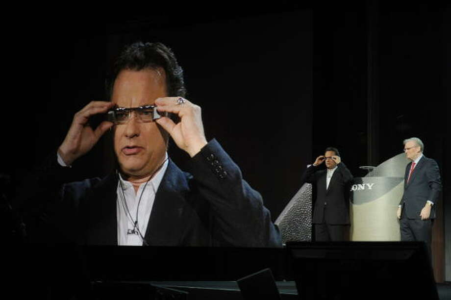 Tom Hanks tries on prototype glasses that allow you to see everything that is in front of you while they display a movie during Sony CEO Howard Stringer's, right, keynote address at the Consumer Electronics Show in Las Vegas Jan. 8. Photo: ROBYN BECK, AFP/Getty Images