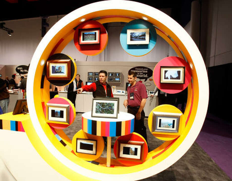 Kodak's Larry Landry, left, shows Nth Degree's Mike Tedeschi Kodak digital picture frames at the Kodak booth at the 2009 International Consumer Electronics Show at the Las Vegas Convention Center Jan. 8. Photo: Ethan Miller, Getty Images