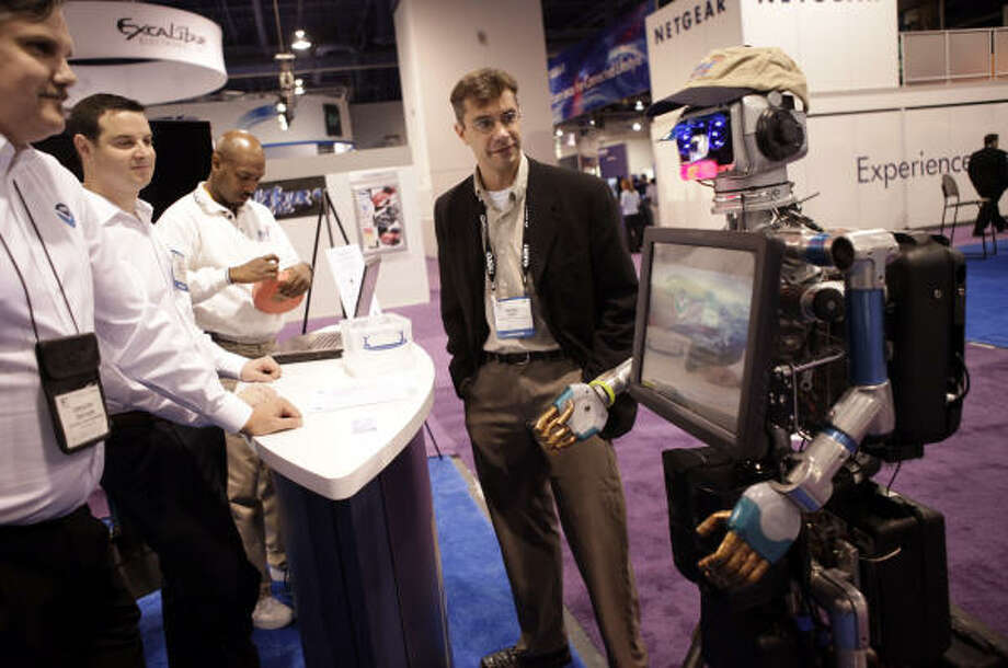 Exhibitors talk to the National Oceanic and Atmospheric Administration's interactive robot, Sunny, right, at the International Consumer Electronics Show in Las Vegas Jan. 8. Photo: Jae C. Hong, AP