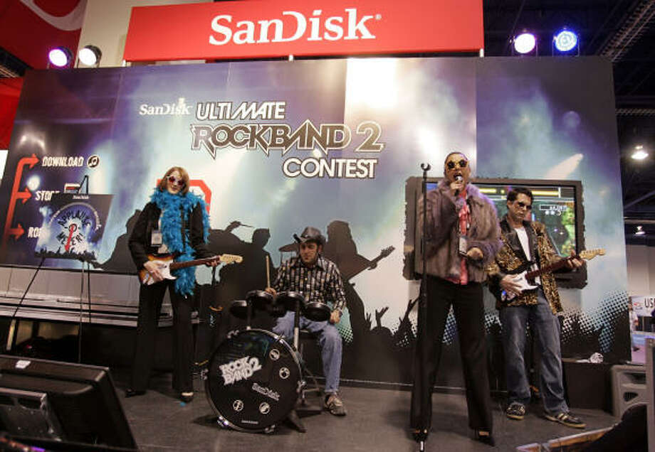 An amateur band plays Rockband 2 that uses the new SanDisk 2 SD card to enhance the playing performance, at the International Consumer Electronics Show in Las Vegas Jan. 8. Photo: Paul Sakuma, AP