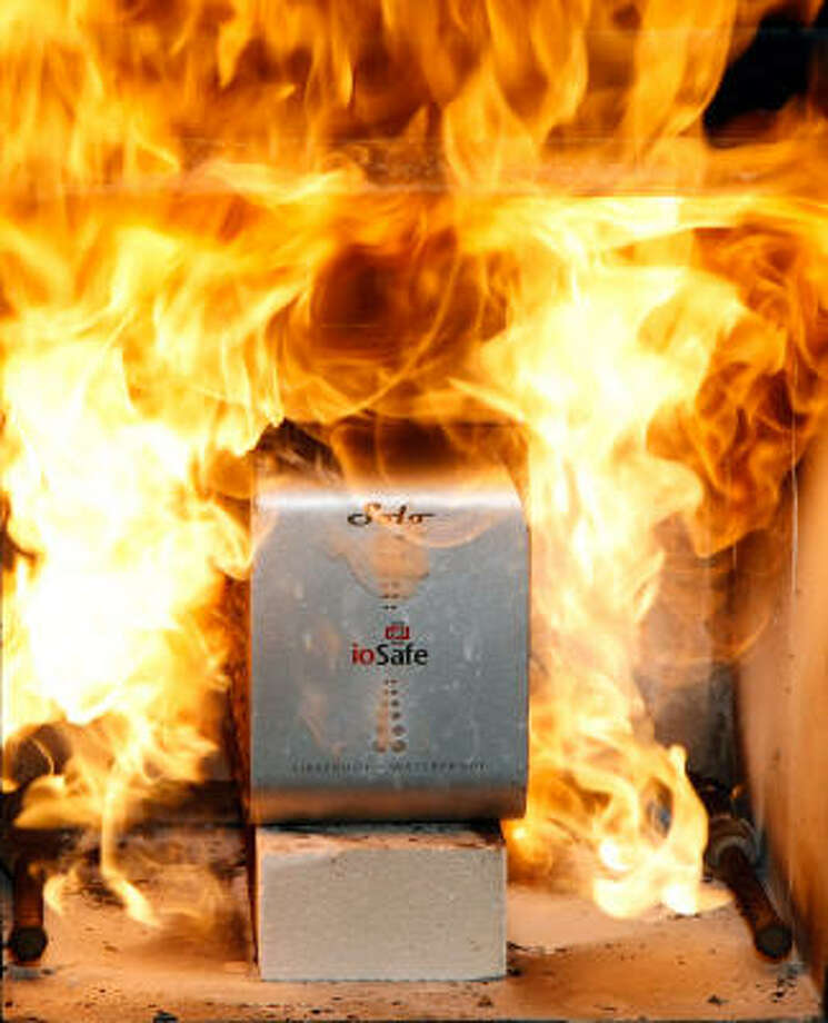 An ioSafe Solo USB external hard drive is set on fire at the 2009 International Consumer Electronics Show. The company says its hard drives are fireproof up to 1,550 degrees for up to 30 minutes and waterproof up to 10 feet of water for 3 days. Photo: Ethan Miller, Getty Images