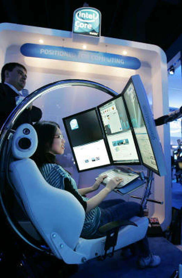 Attendee Sarena Yang uses the Gravitonus seat in the Intel booth at the International Consumer Electronics Show in Las Vegas Jan. 8. The Gravitonus seat has several computer screens and rotates and uses the Intel Core chip. Photo: Paul Sakuma, AP