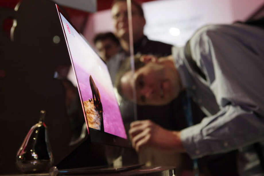 Scott Charles, of Eugene, Ore.,  takes a closer look at LG's OLED TV at the International Consumer Electronics Show in Las Vegas on Jan. 8. Photo: Jae C. Hong, AP