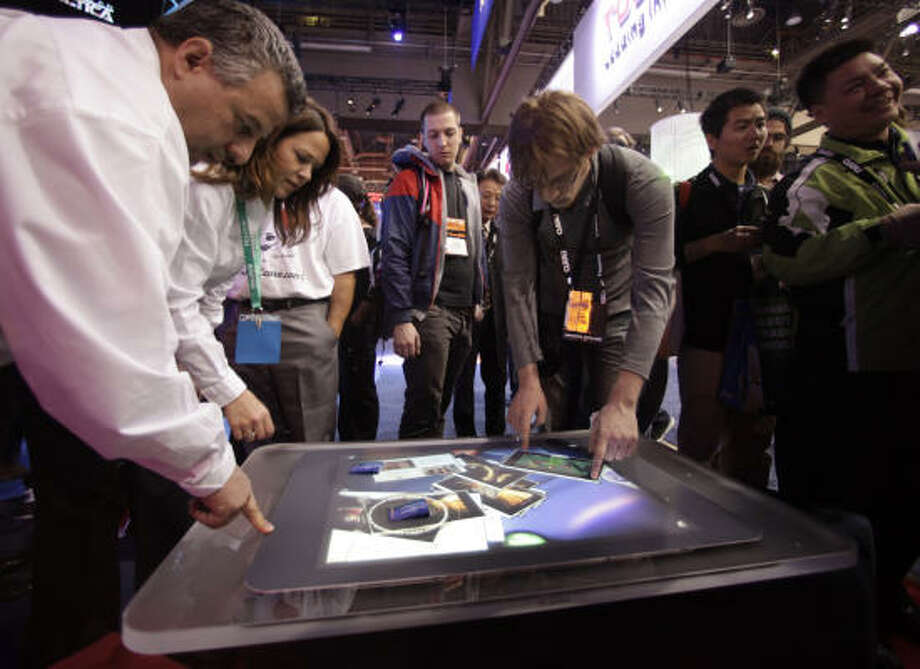 Show attendees play with a Microsoft Surface table at the International Consumer Electronics Show in Las Vegas Jan. 8. Photo: Jae C. Hong, AP