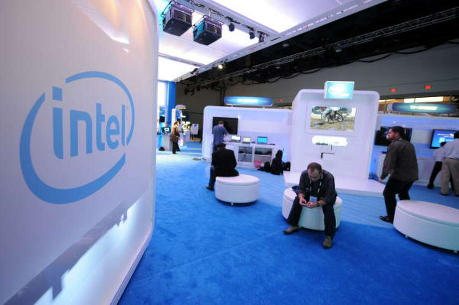 People sit in the Intel display during set up. Photo: ROBYN BECK, AFP/Getty Images