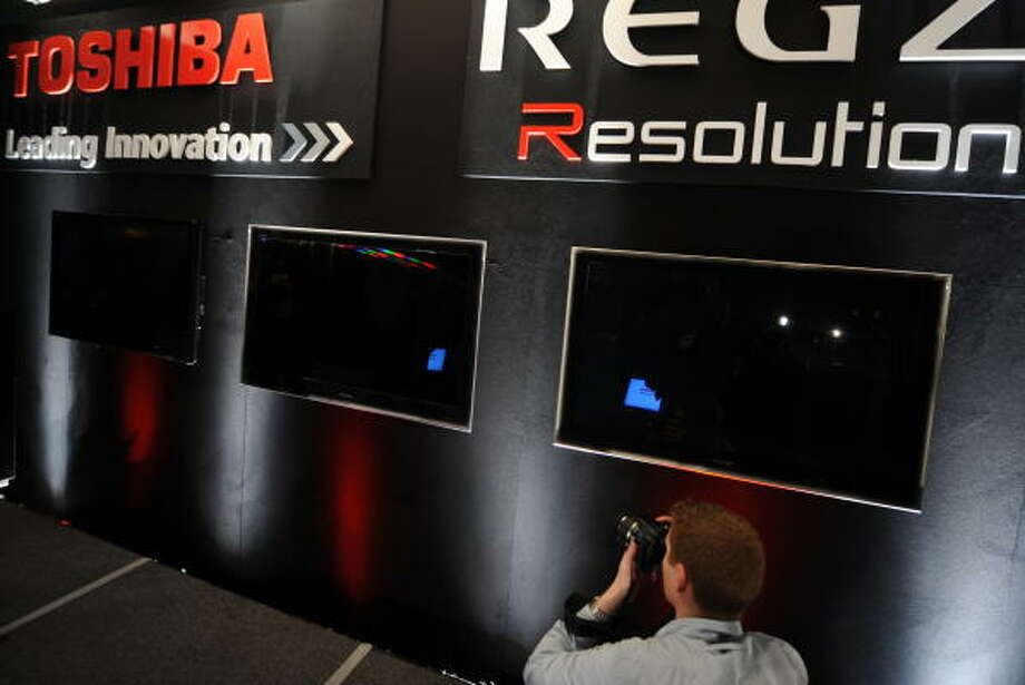 A member of the media photographs some of the new televisions presented by Toshiba. Photo: ROBYN BECK, AFP/Getty Images