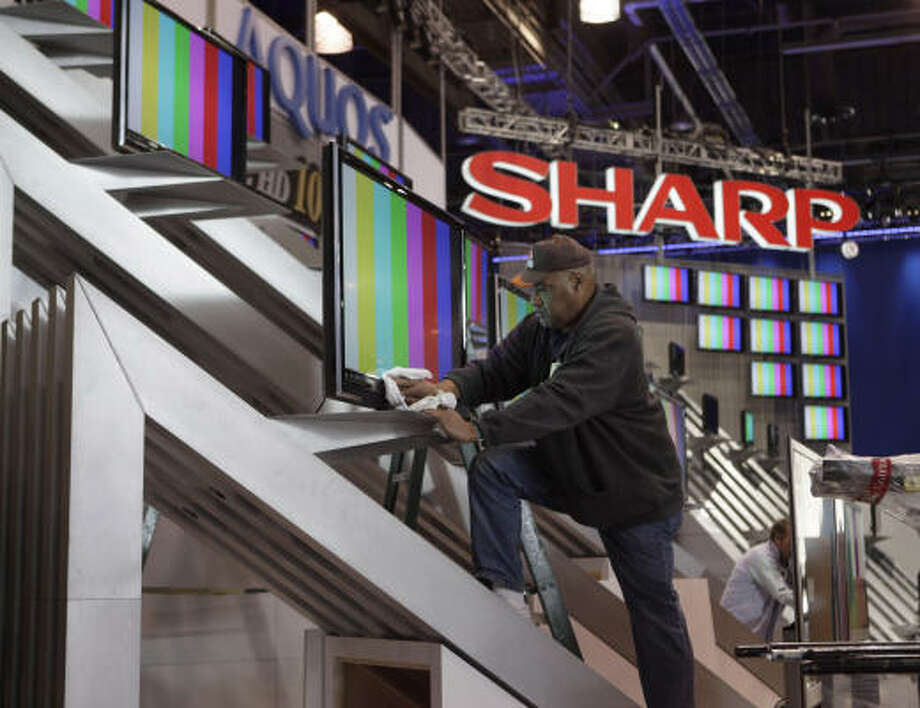 Electrician Douglas Reid wipes dust off a LCD display at the Sharp booth. Photo: Jae C. Hong, AP