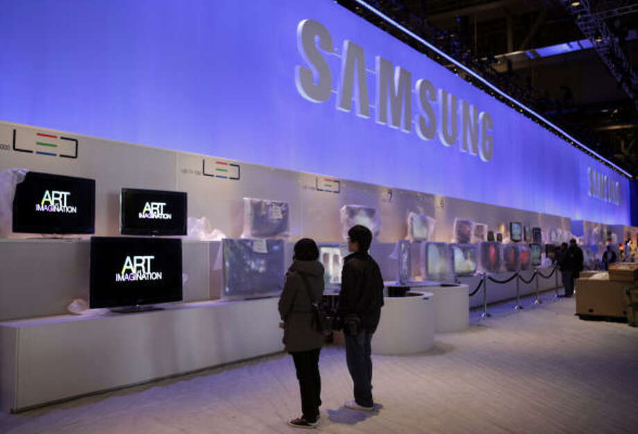Exhibit workers look at LCD displays at the Samsung booth. Photo: Jae C. Hong, AP
