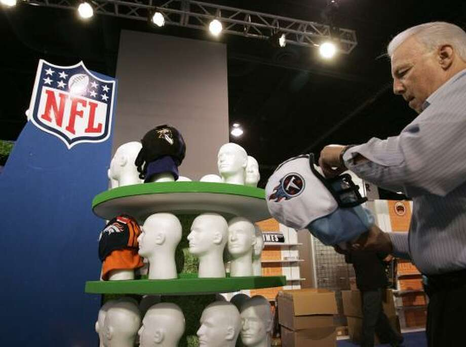 Excalibur Electronics' Jerry Cohen works on a Tennessee Titans mask at the company's booth. Excalibur makes officially licensed games and other products from the NFL and other companies. Photo: Paul Sakuma, AP