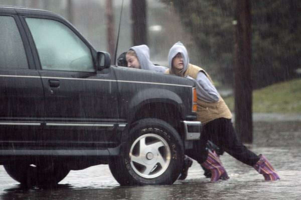 A group pushes a car out of a street on Jan. 8 where it stalled a day earlier in flood waters in Snoqualmie, Wash.