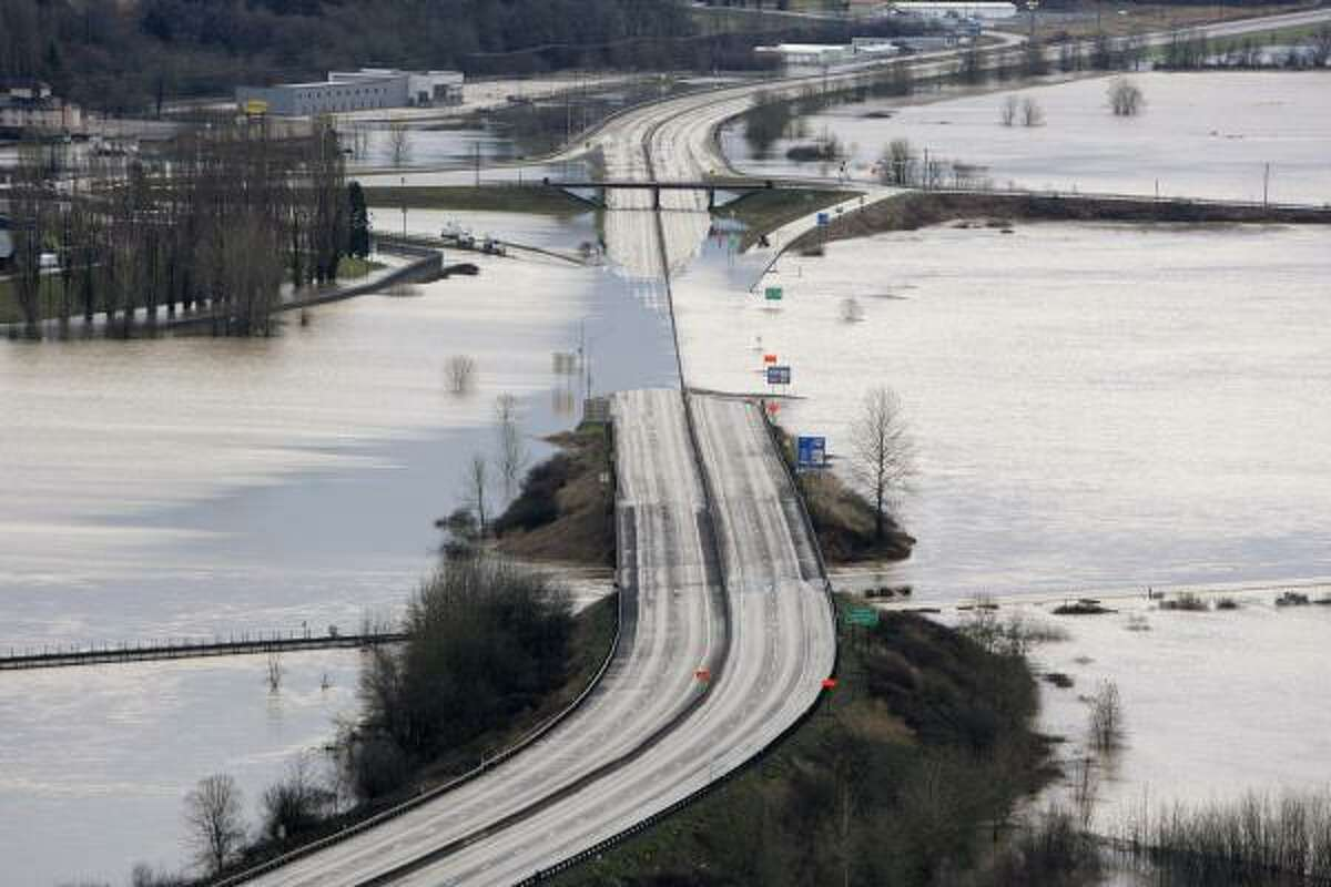 Interstate 5 is covered by the flooding Chehalis River Thursday morning in Chehalis, Wash.