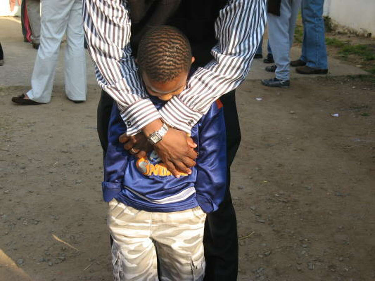 The arms of the Rev. Marcus D. Cosby of Houston's Wheeler Avenue Baptist Church cradle a young boy at Berea Baptist Church in Johnnasburg.