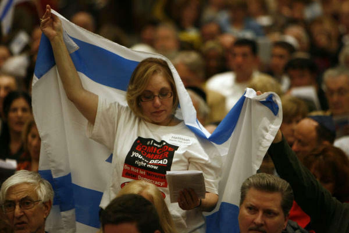 Linda Pravda Horowitz of Houston reads as she holds up an Israeli flag at Congregation Beth Yeshurun on Wednesday in Houston.