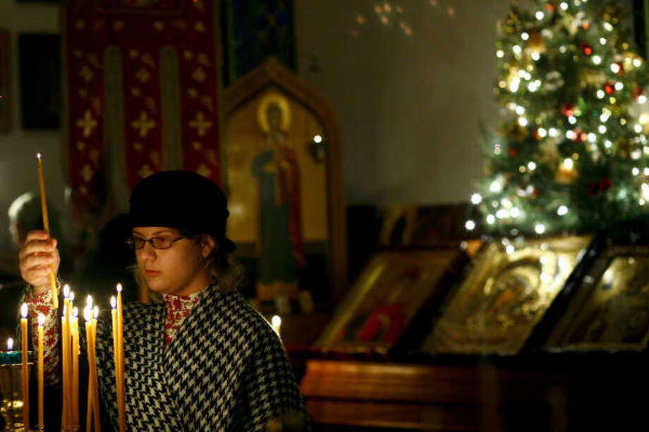 Natalia Kupec, 14, lights a prayer candle during the church's Christmas Eve service. Photo: Michael Paulsen, Chronicle