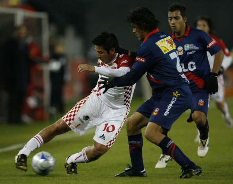 UAG Tecos defender Mario Ortiz, left, tries to make a move on Morelia defender Mauricio Romero in the first half. Photo: Julio Cortez, Chronicle