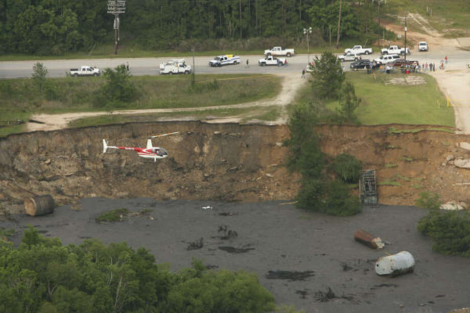 May 7, 2008:Hazardous Materials workers inspect the sinkhole from a helicopter. City officials estimate the size of the hole at about 200 yards wide and as much as 100 feet deep in places. Photo: James Nielsen, Chronicle