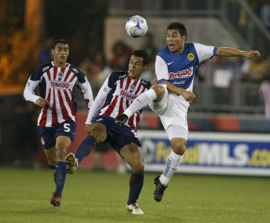 Club America 1, Chivas 1Club America forward Salvador Cabanas, right, goes up for the ball against Chivas del Guadalajara defender Mario de Luna, center, as teammate Patricio Araujo, left, tries to join in on the action. Photo: Julio Cortez, Chronicle