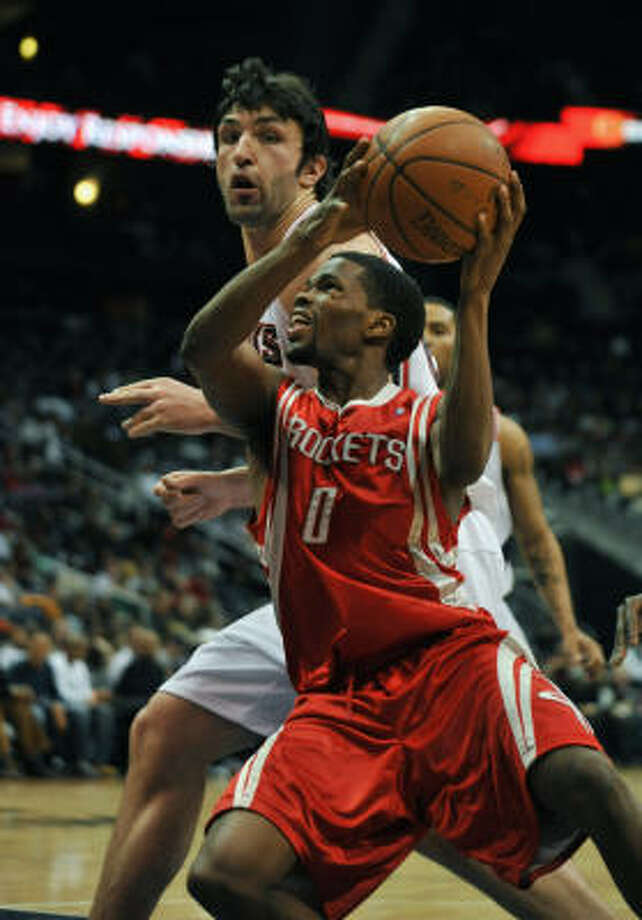 Aaron Brooks (0) drives to the basket against Hawks forward Zaza Pachulia in the fourth quarter. Photo: Gregory Smith, AP