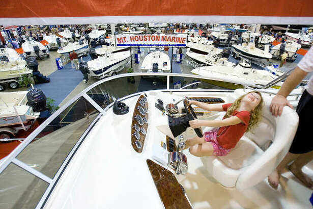 Sage Pollock, 6, pretends to drive one of the boats on display Saturday at the Houston International Boat, Sport & Travel Show at the Reliant Center.