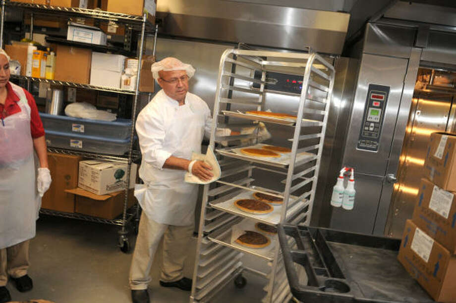 Something new: Bakery partner Juan Molina takes a rack of pies out of the oven at the new H-E-B Spring Market store. Photo: Jerry Baker, For The Chronicle