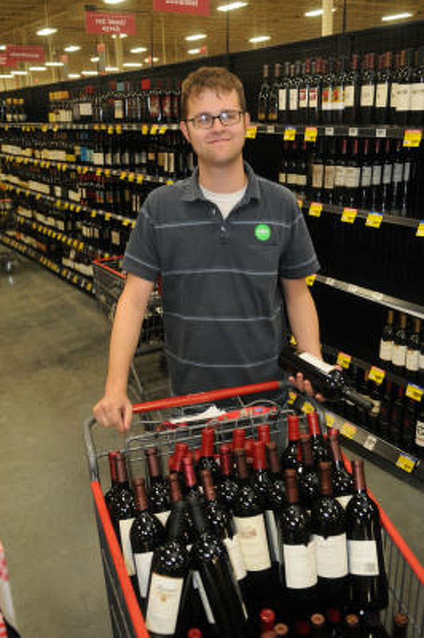 Wine steward David Ely shows off some of collection at the new H-E-B Spring Market store.