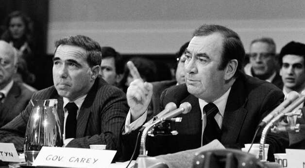 In this Oct. 21, 1975 file photo, New York Gov. Hugh L. Carey, right, and Felix Rohatyn, chairman of Municipal Assistance Corporation, press members of a House economic stabilization subcommittee in Washington, to enact legislation to aid deficit-ridden New York City. Carey, who led the rescue effort that brought New York City back from the brink of bankruptcy during its 1975 fiscal crisis, died Sunday, Aug. 7, 2011. He was 92. (AP Photo/Charled Gorry, File) Photo: Charles Gorry / AP1975