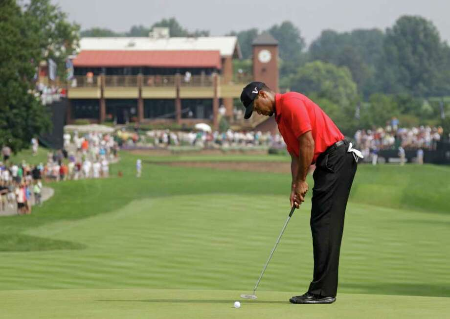 Tiger Woods taps in his par putt on the first hole during the final round of the Bridgestone Invitational golf tournament at Firestone Country Club in Akron, Ohio, Sunday, Aug. 7, 2011. (AP Photo/Mark Duncan) Photo: Mark Duncan, STF / AP