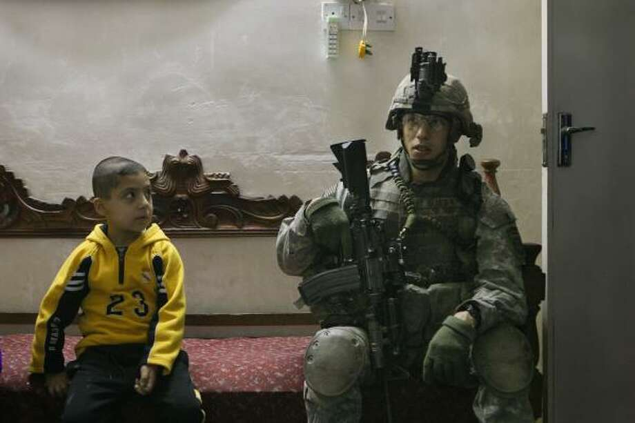 During a house search in north Baghdad on Sunday, an Iraqi boy studies a U.S. soldier of the 2nd Battalion, 319th Airborne Field Artillery Regiment. Dozens were killed in attacks that day. Photo: ANJA NIEDRINGHAUS, ASSOCIATED PRESS