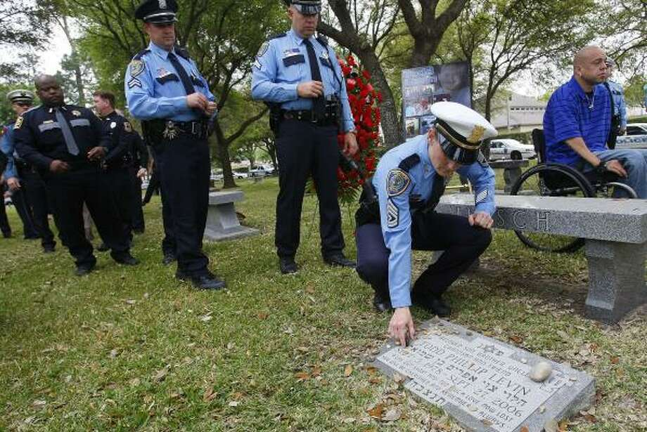 Sgt. Teresa Curry places a pebble on the grave of Todd Levin, who died in a 2006 vehicle crash. Levin's girlfriend was also killed in the wreck. The driver of the other vehicle was charged with two counts of intoxication manslaughter and sentenced to 10 years in prison. Photo: MAYRA BELTRÁN, CHRONICLE