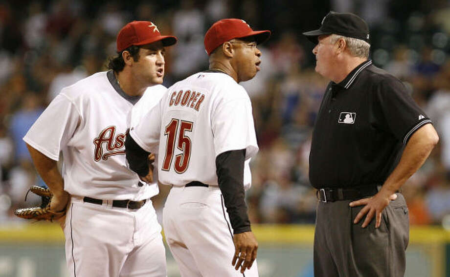 Lance Berkman, left, and manager Cecil Cooper dispute a call with umpire Tim Welke against the Cardinals in June. Photo: James Nielsen, Houston Chronicle