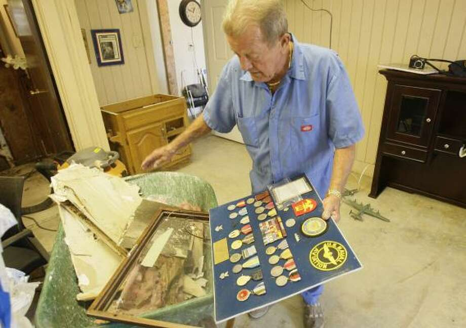 Eddie Janek looks at his shadow box of medals and mementos from World War II and the Korean War. Ike washed them away to Pelican Island, about five miles from his Galveston home. Photo: MELISSA PHILLIP, CHRONICLE