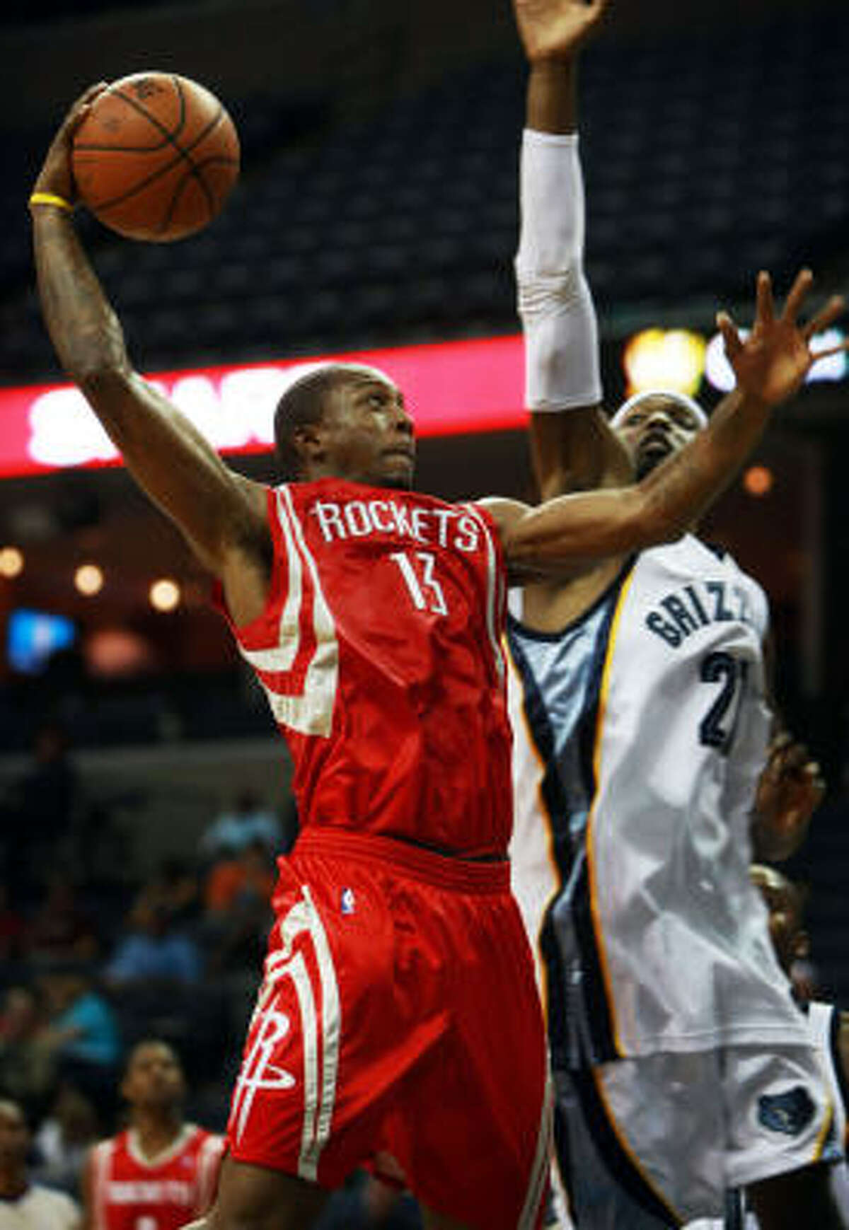 Rockets guard Von Wafer, left, looks to dunk over Memphis Grizzlies forward Hakim Warrick in the second half on Wednesday in Memphis, Tenn.