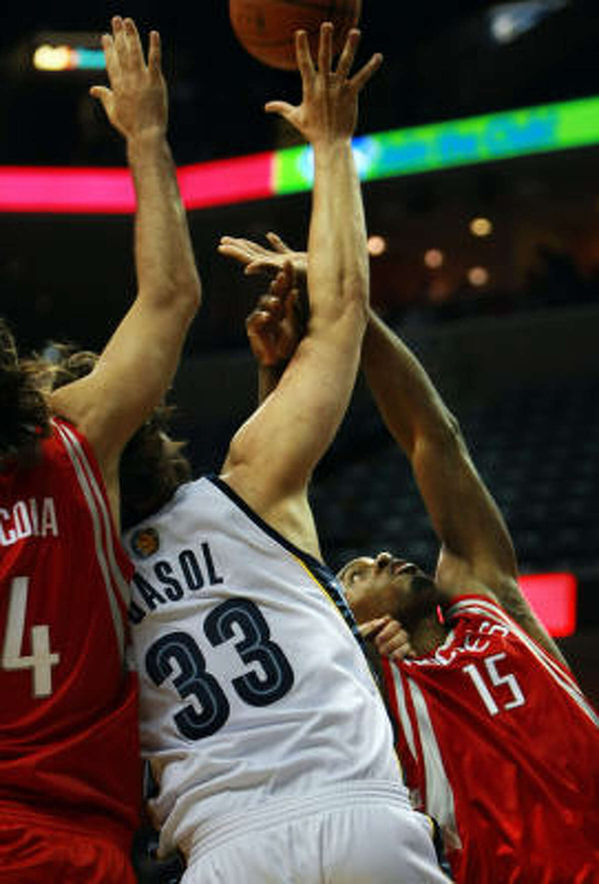 Rockets forward Joey Dorsey (15) battles for a rebound with Memphis Grizzlies center Marc Gasol (33), backed up by Rockets forward Luis Scola (4), in the first half on Wednesday in Memphis, Tenn.