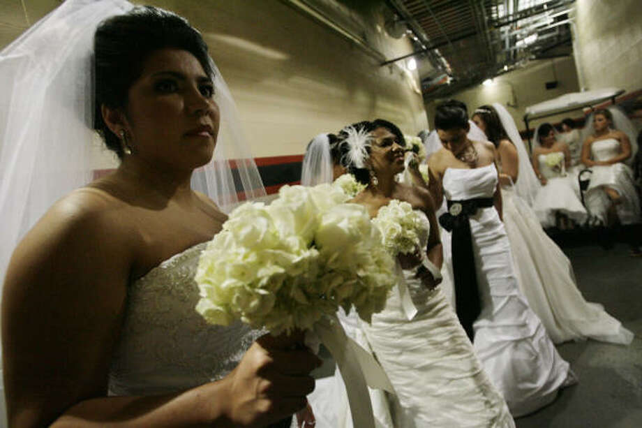 Jo Rodriguez, left, Gabrelle Cathey and Greer Van Buren wait to wed at Minute Maid Park on Sunday. Their wedding venues had to file for bankruptcy. Photo: Eric Kayne, Chronicle