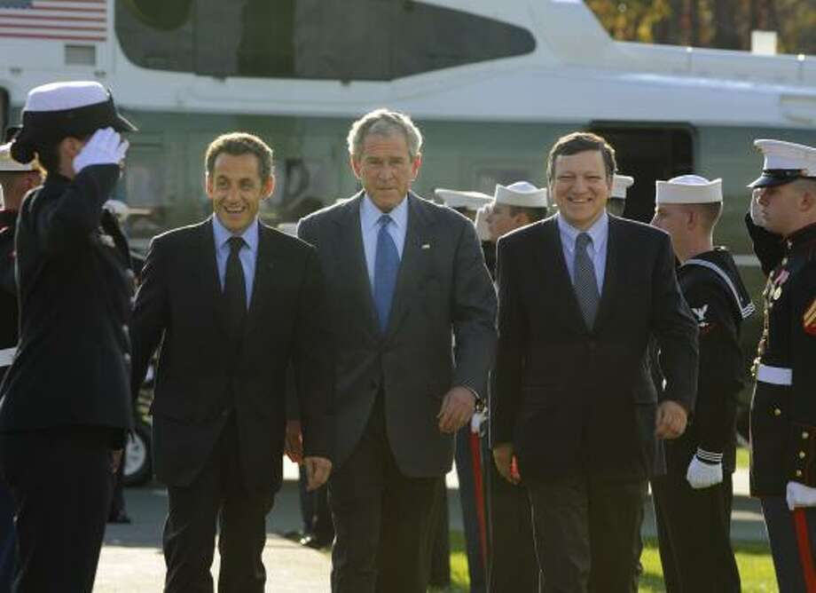 President Bush escorts French President Nicolas Sarkozy, left, and Jose Manuel Barroso, president of the European Commission, after they arrived Saturday at Camp David, Md. Photo: MIKE THEILER, AFP/GETTY IMAGES