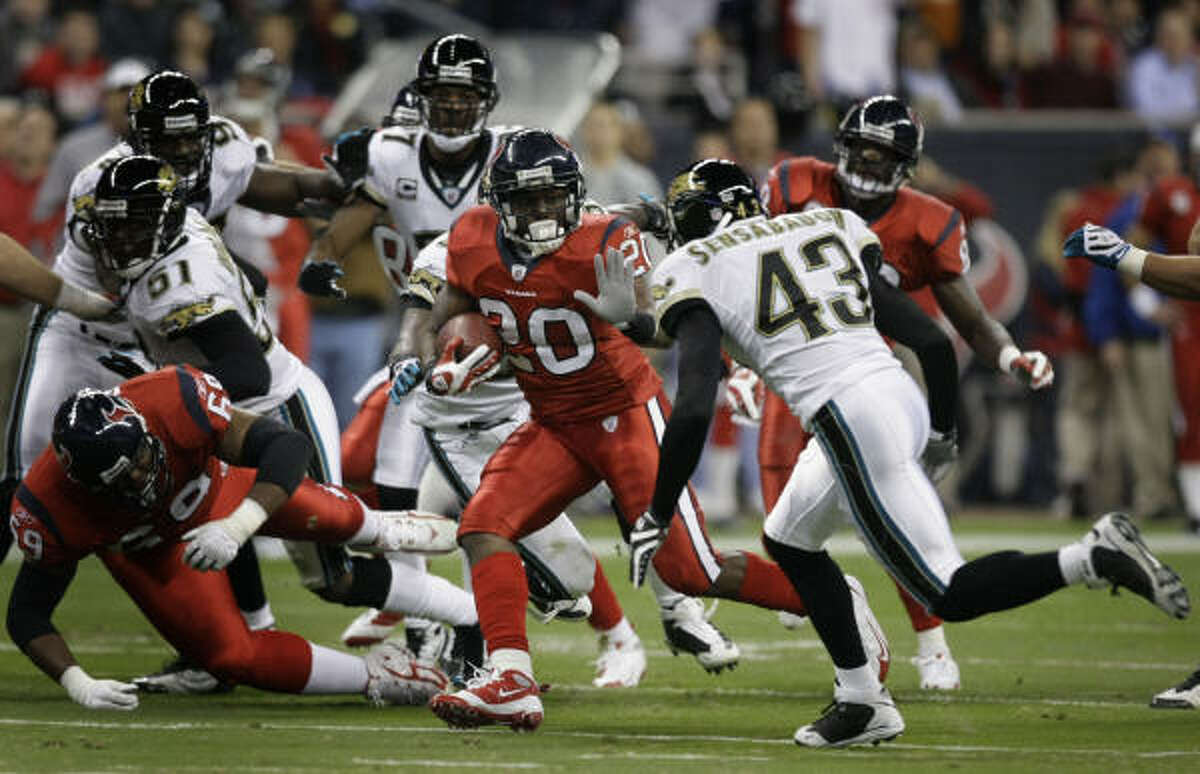 Texans running back Steve Slaton (20) runs past Jaguars safety Gerald Sensabaugh (43) during the first quarter.