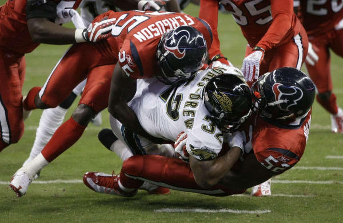 Texans linebacker Xavier Adibi (52) and safety Nick Ferguson (25) combine to bring down Jaguars running back Maurice Jones-Drew (32) during the first quarter.