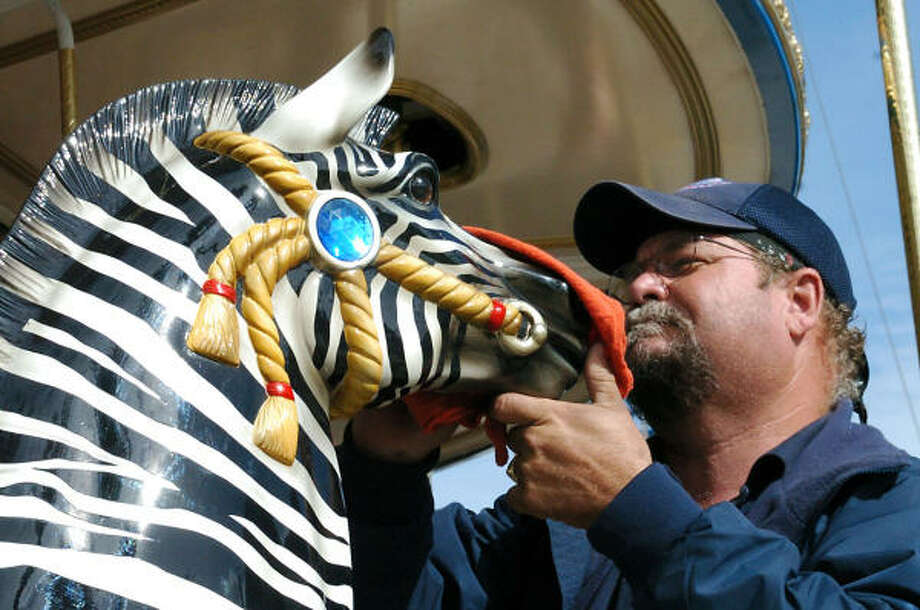Kemah Boardwalk Maintenance Manger John Horton puts a finishing touch on a carousel zebra as the ride preparee to open Dec. 15. Photo: Kirk Sides, For The Chronicle