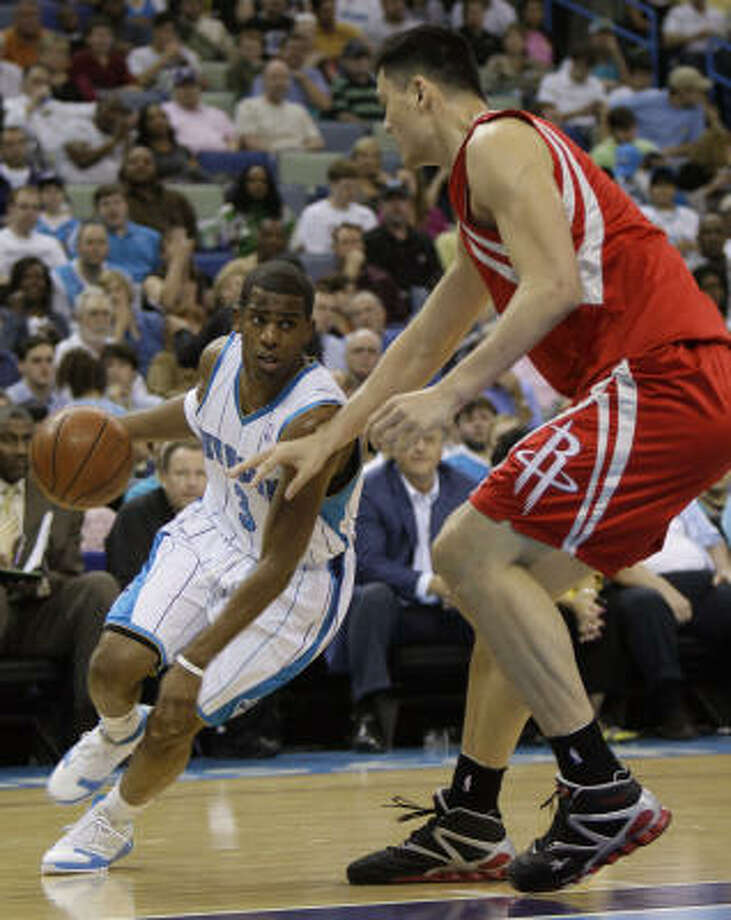 Hornets guard Chris Paul, left, drives past Yao Ming in the first half. Photo: Alex Brandon, AP