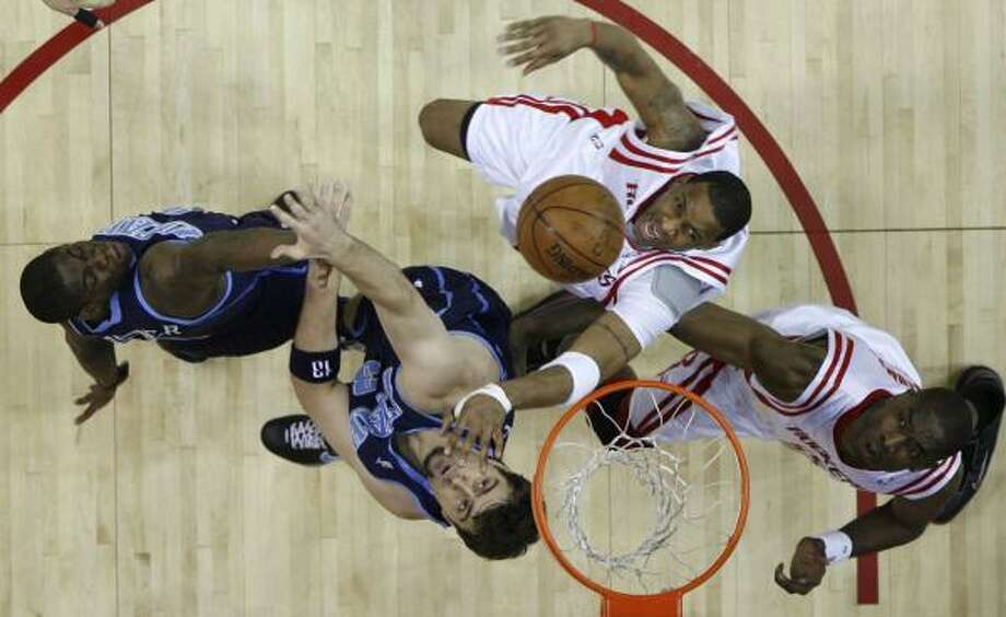 Tracy McGrady, center, and Dikembe Mutombo, right, fight for a rebound with Utah's Mehmet Okur and Ronnie Brewer, far right. Photo: JAMES NIELSEN, CHRONICLE