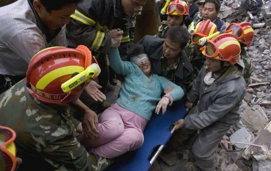 Zhang Xiaoyan, 34, eight months pregnant, is pulled from a damaged apartment after Monday's magnitude-7.9 earthquake in Dujiangyan, China. At right, survivors walk along a mountain road, which is the only escape route from the earthquake epicenter in Wenchuan. Photo: NG HAN GUAN, ASSOCIATED PRESS
