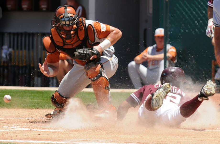 Texas catcher Cameron Rupp, left, loses the ball as A&M's Kyle Colligan scores in the third inning. Photo: Dave McDermand, AP