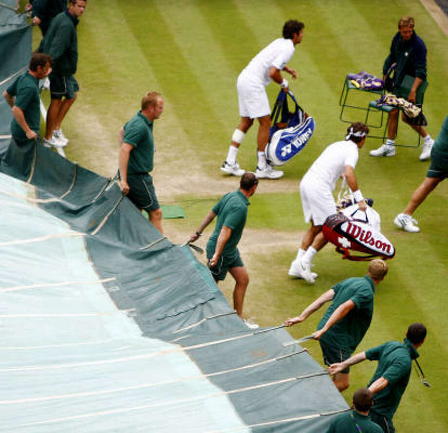 Mario Ancic and Roger Federer leave Centre Court for a rain delay. Photo: Sean Dempsey, AP