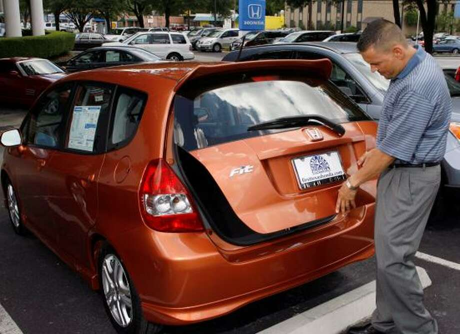 Shane Gilbert prepares a Honda Fit for a customer at an Austin dealership. Honda's long-term emphasis on small, fuel-efficient vehicles positioned it well in June, when it reported a sales increase as competitors saw declines. Photo: HARRY CABLUCK, ASSOCIATED PRESS