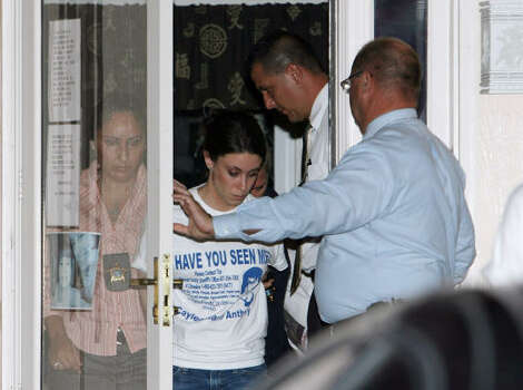 Casey Anthony, center, in handcuffs, walks out her home after being taking in custody by Orange County Sheriff's detectives John Allen, right, and Yuri Melich, second from right, Friday, Aug. 29, 2008 in Orlando, Fla. Photo: Red Huber, AP