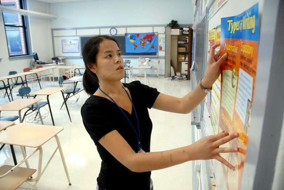 Dinh Vong, a new teacher at Ryan Middle School, spruces up her classroom at the revamped facility. Only 10 of the school's 40 teachers from last year were rehired. Photo: DAVE ROSSMAN, FOR THE CHRONICLE