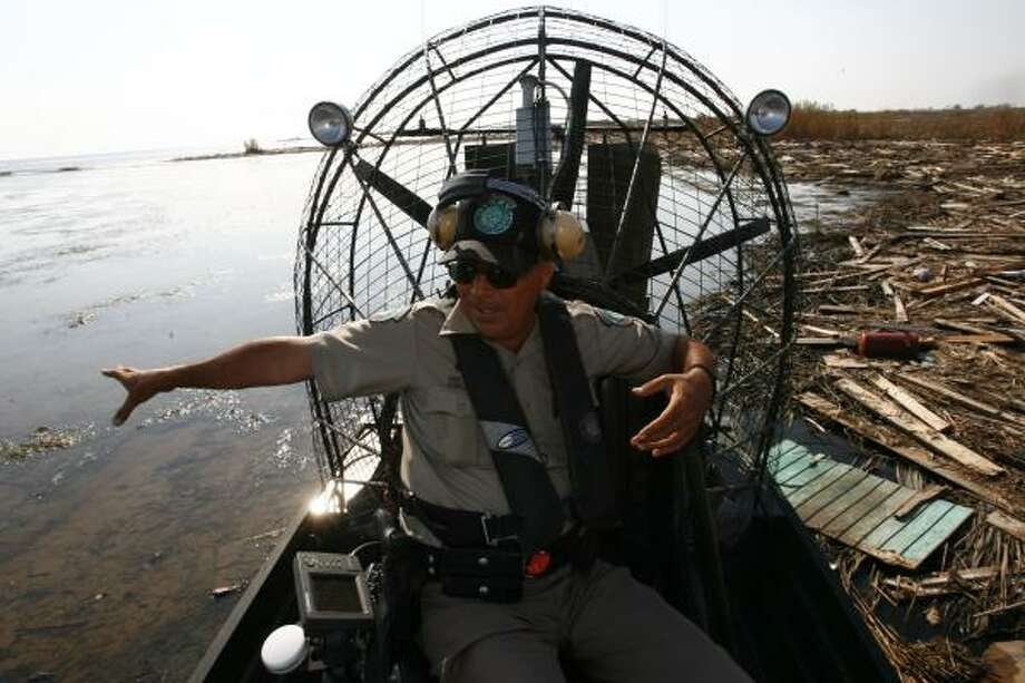Texas Parks and Wildlife game warden Hector Gonzalez uses his 350-horsepower airboat Tuesday to skim across two inches of water, avoiding alligators and snakes in this debris field in Chambers County. Photo: SHARÓN STEINMANN, CHRONICLE