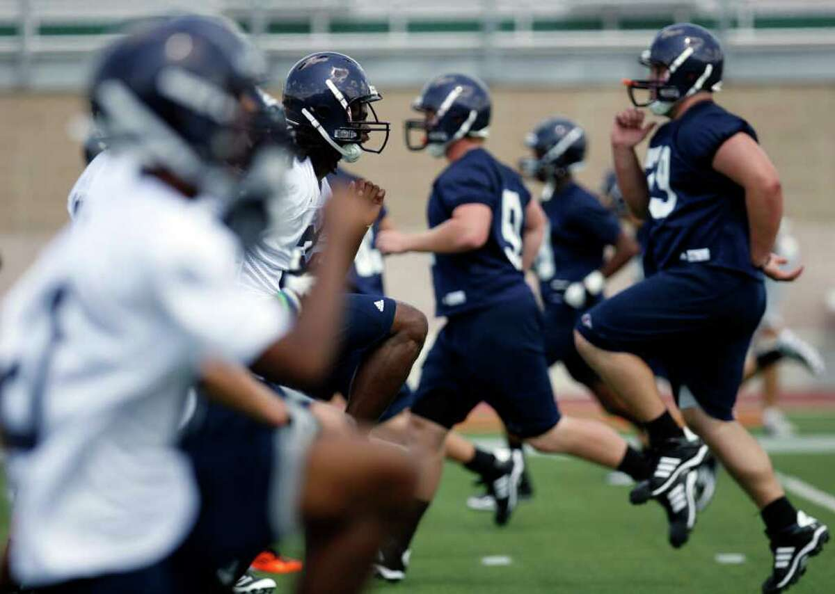 UTSA players loosen up in sizzling conditions during the Roadrunners' first fall practice on Sunday, August 7, 2011 at Farris Stadium.