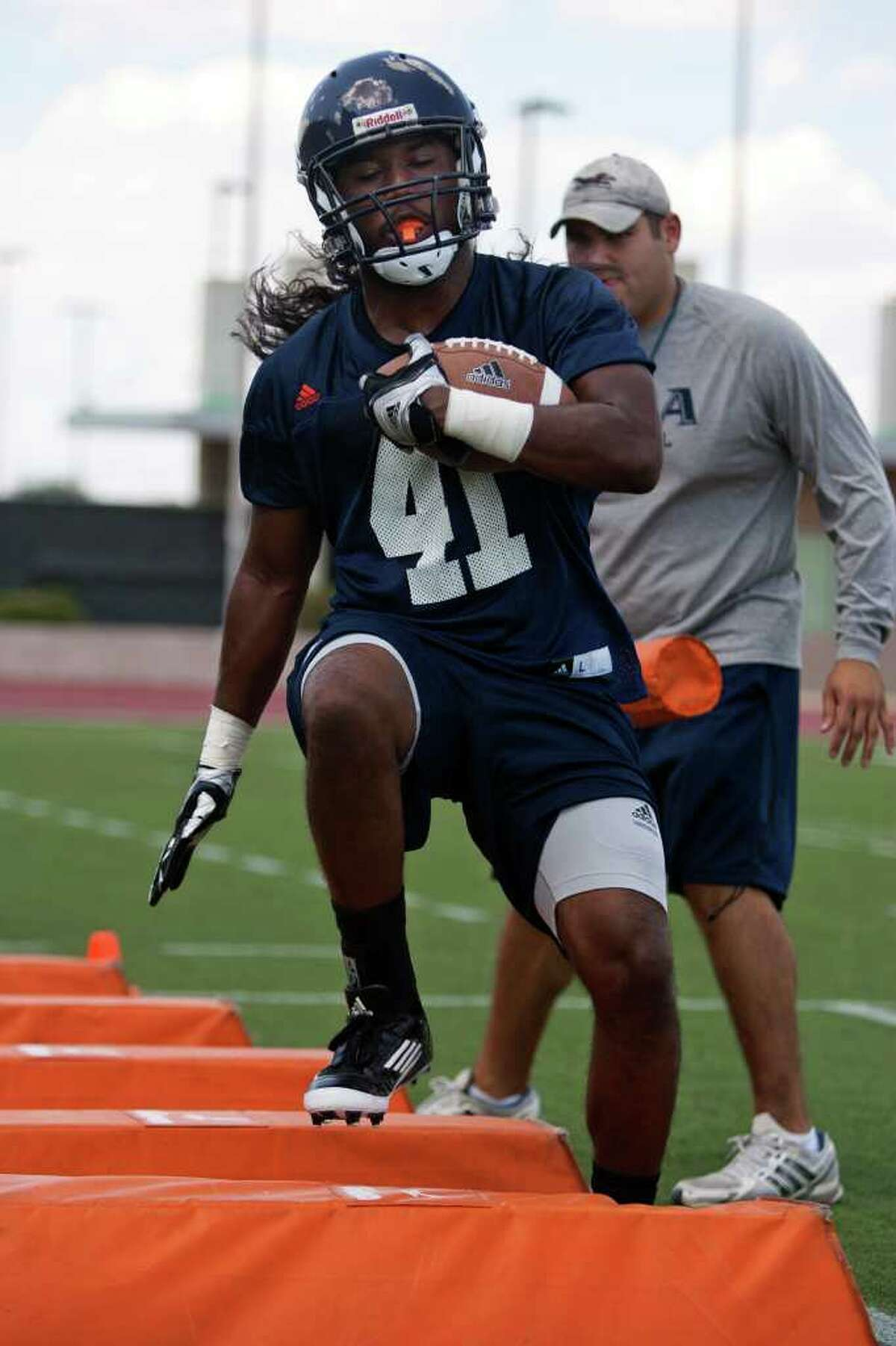 UTSA running back CheRod Simpson (41) runs a drill in front of running backs coach Polo Gutierrez during the Roadrunners' first fall practice on Sunday, August 7, 2011 at Farris Stadium. Simpson is a sophomore walk-on from Oakland, Calif., who spent a semester at Texas A&M-Commerce.