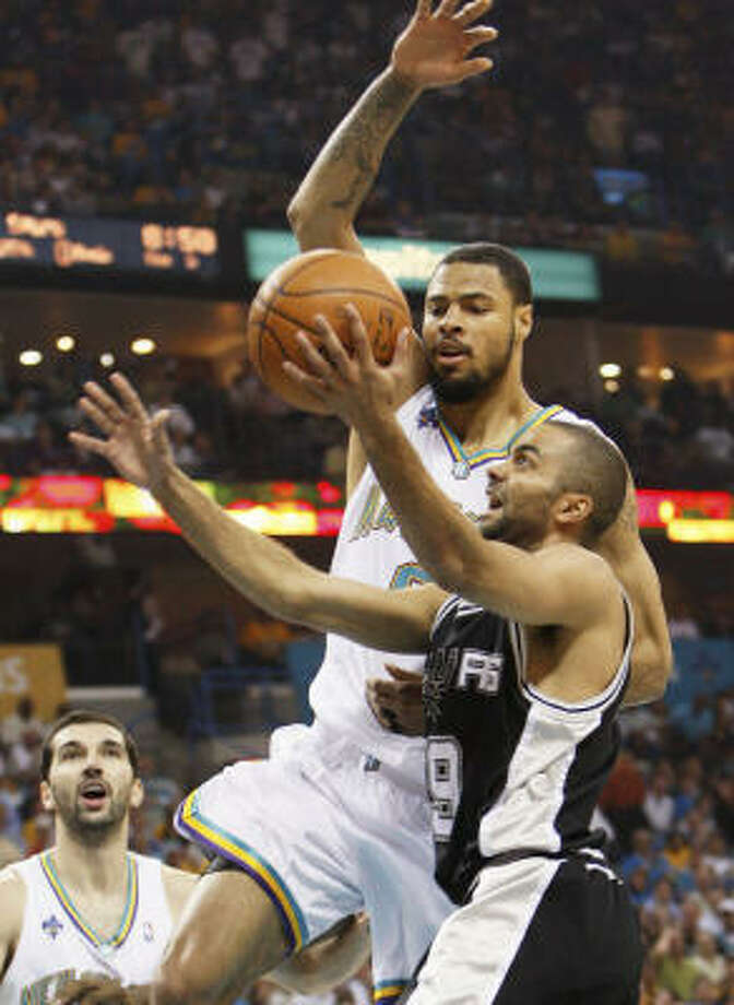 Spurs guard Tony Parker goes to the basket as Hornets center Tyson Chandler defends in the first half. Photo: Ann Heisenfelt, AP